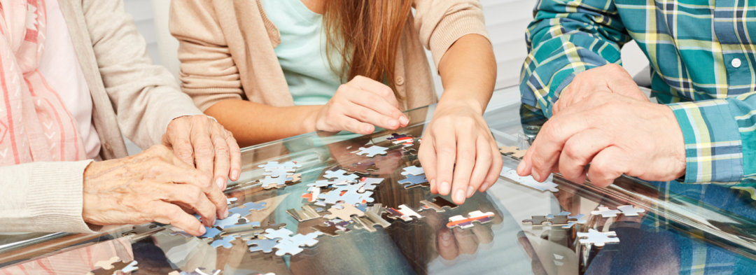 elders with caregiver solving the jigsaw puzzle