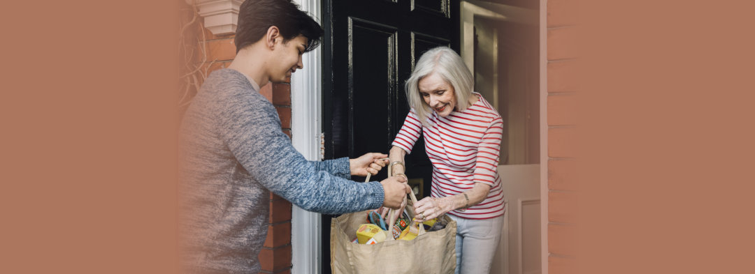 young man giving a pack of grocery to a senior woman